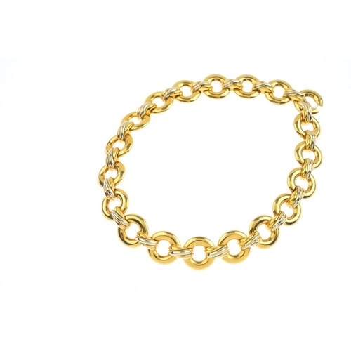 303 - CARTIER - a 'Trinity' necklace. Comprising a series of nineteen circular links, with interwoven tri-...