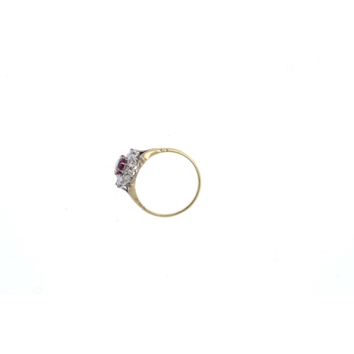 309 - A Thai ruby and diamond cluster ring. The oval-shape ruby, with brilliant-cut diamond surround and b...