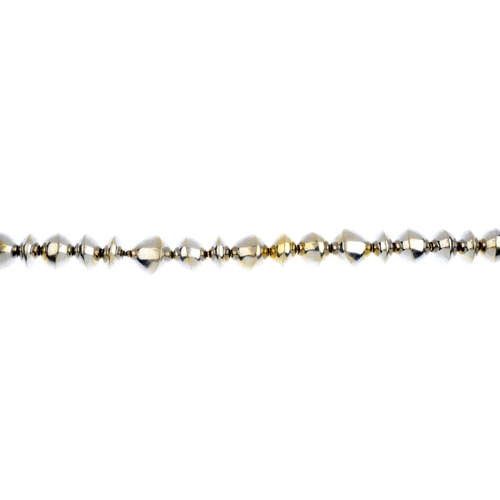 312 - A bracelet. Comprising a series of vari-width beads, each tapered to an asymmetric knife-edge line. ...