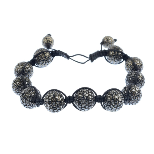 315 - A 'coloured' diamond bracelet. Designed as a series of eleven pave-set 'black' diamond spheres, conn...