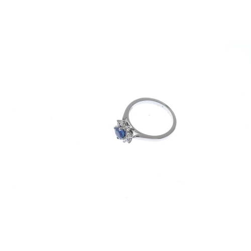 318 - An 18ct gold sapphire and diamond cluster ring. The circular-shape sapphire, with brilliant-cut diam...