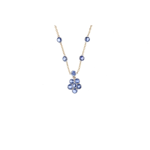 321 - A sapphire necklace. Of bi-colour design, the circular-shape sapphire floral cluster, suspended from...