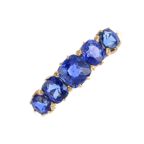 323 - A sapphire five-stone ring. The graduated cushion-shape sapphire line, with tapered shoulders. Total...