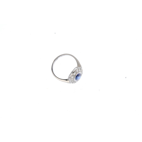 329 - A sapphire and diamond cluster ring. The oval-shape sapphire, with single-cut diamond surround and s...