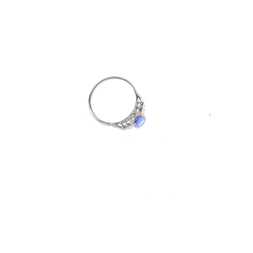 331 - An 18ct gold sapphire and diamond ring. The oval-shape sapphire, with baguette-cut diamond stepped s...