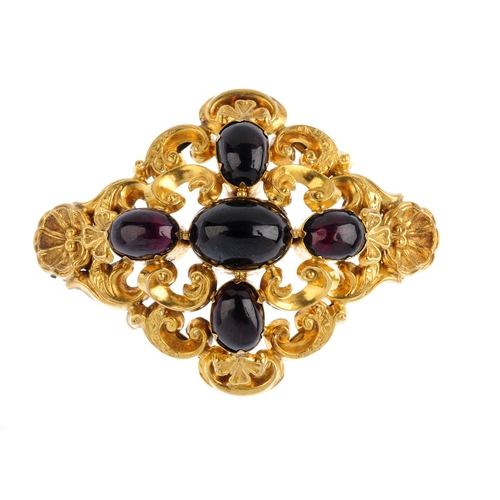 333 - A mid Victorian gold garnet brooch. Designed as an oval garnet cabochon cross, with scrolling foliat...