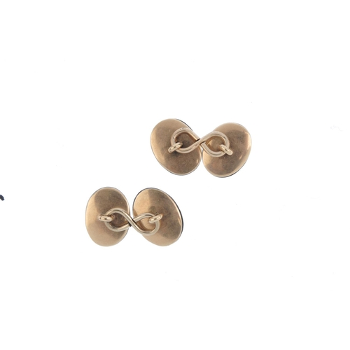 335 - A pair of onyx cufflinks. Each designed as an oval black onyx cabochon, with similarly-designed reve...