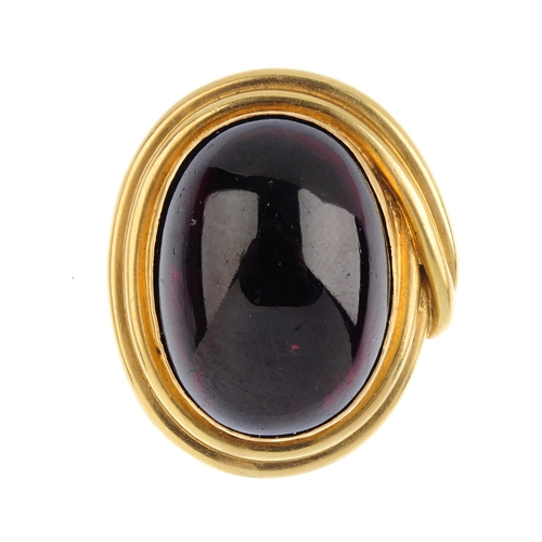 336 - A garnet brooch. The oval garnet cabochon, with grooved crossover surround. Length 3.5cms. Weight 16...