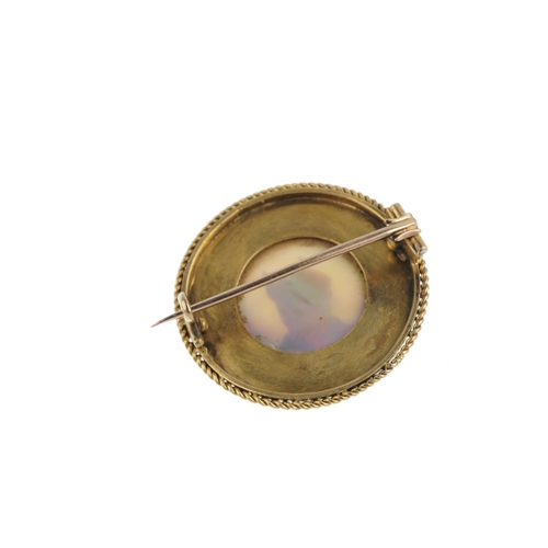 339 - A reverse-carved intaglio dog brooch. The circular rock crystal cabochon, carved and painted to depi...