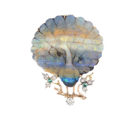 34 - A boulder opal and gem-set brooch. The boulder opal doublet carved to depict a peacock, atop an old-...