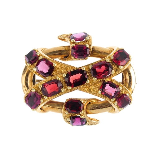 343 - A gold garnet knot brooch. Designed as an octagonal and oval-shape garnet textured ribbon, scrolling...