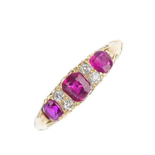 347 - A ruby and diamond ring. The graduated cushion-shape ruby line, with old-cut diamond double spacers ...