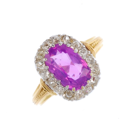 355 - A Ceylon sapphire and diamond cluster ring. The cushion-shape pink sapphire, weighing 2.46cts, with ...