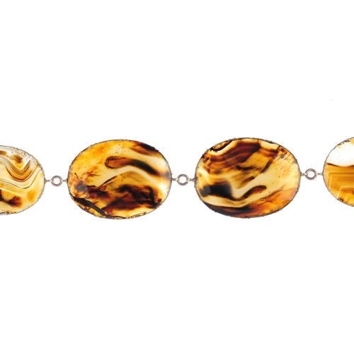 357 - An agate bracelet. Designed as a series of oval-shape agate collets, with concealed push-piece clasp...