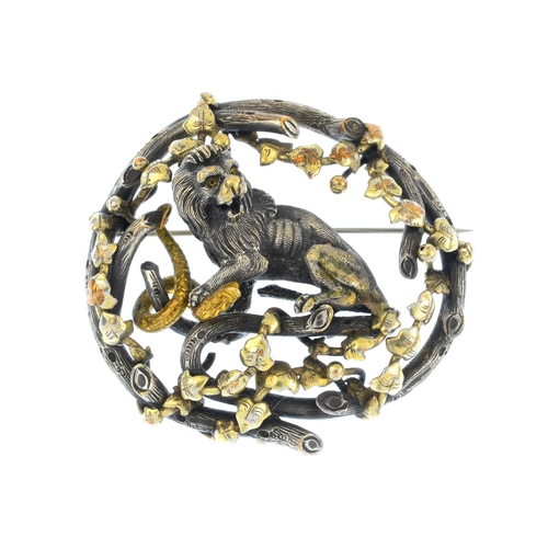 358 - A late Victorian lion brooch. Of bi-colour design, the textured lion pinning down a snake, with vine...