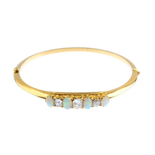 36 - An early 20th century 15ct gold opal and diamond hinged bangle. The alternating oval opal cabochon a...
