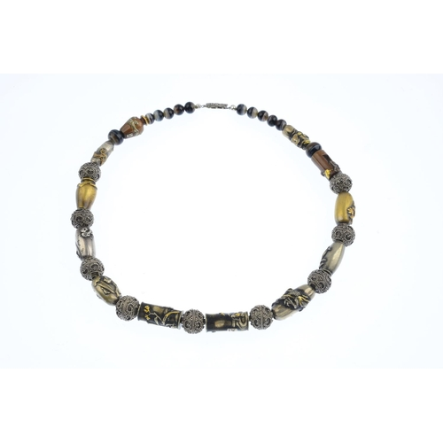 361 - An ojime bead necklace. The ojime, including depictions of dragons, fish and vases, with cannetille ...