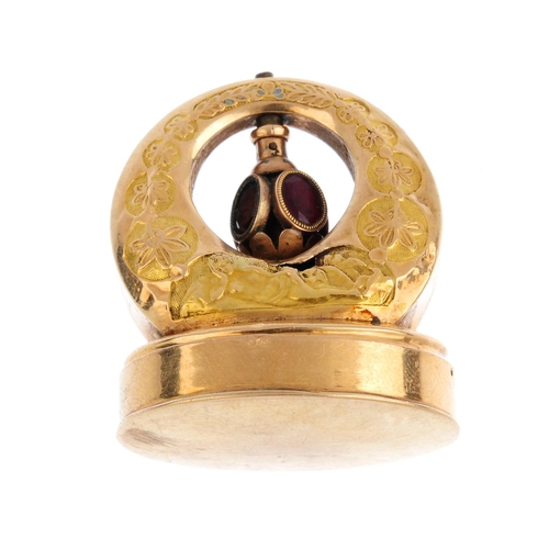 364 - An early Victorian gold musical fob. The oval base, on a crescent surmount embossed with a reclining...
