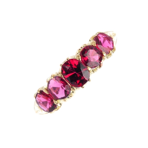 369 - A spinel five-stone ring. The graduated oval-shape red spinel line, with tapered shoulders. Total sp...