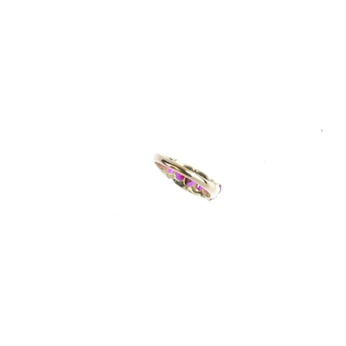 373 - A ruby five-stone ring. Designed as a graduated oval-shape ruby line, with scrolling gallery and sho...