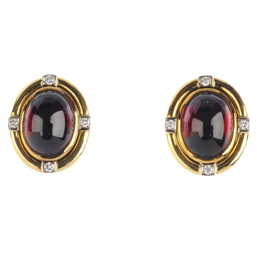 376 - A pair of garnet and diamond earrings. Each designed as an oval garnet cabochon, within a brilliant-...