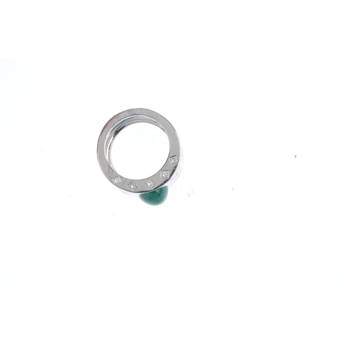 381 - An emerald and diamond band ring. The oval emerald cabochon, inset to the polished band, with simila...