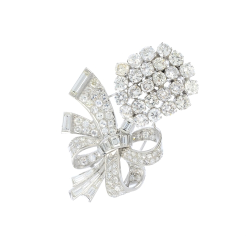 385 - A diamond floral spray brooch. Designed as a brilliant and baguette-cut diamond bouquet, gathered to...