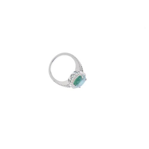 386 - An 18ct gold emerald and diamond cluster ring. The oval-shape emerald, with brilliant-cut diamond su...