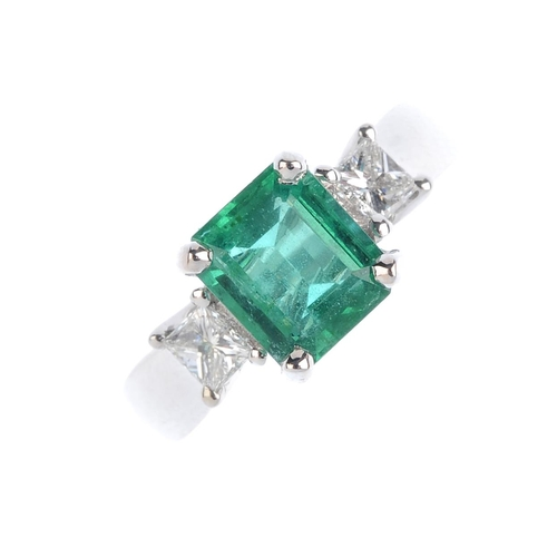 389 - An emerald and diamond dress ring. The rectangular-shape emerald, with square-shape diamond shoulder...