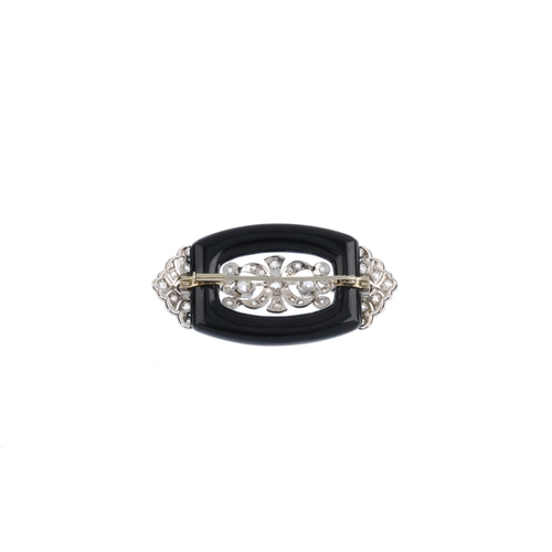 393 - A diamond and onyx brooch. The curved rectangular-shape onyx, supporting an old and rose-cut diamond...