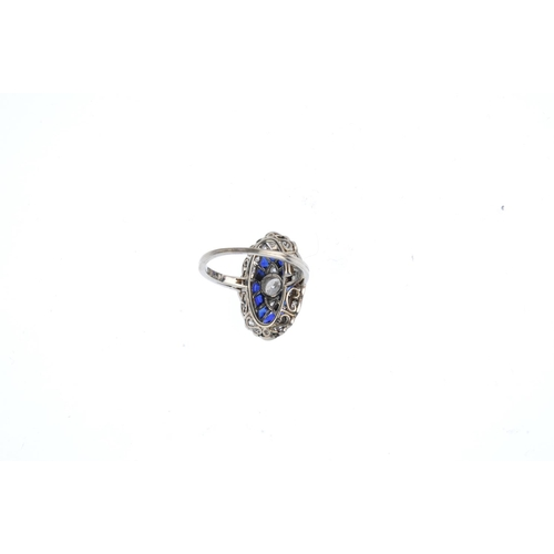 397 - A synthetic sapphire and diamond ring. The vari-cut diamond collet and sides, with calibre-cut synth...