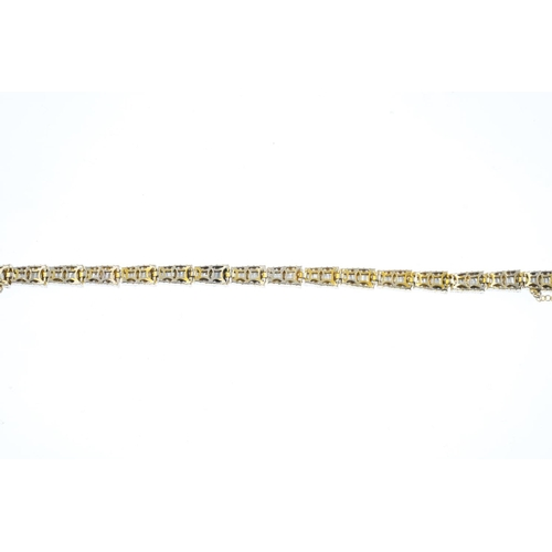 398 - An 18ct gold diamond bracelet. Designed as a series of tapered panels, each comprising a baguette-cu...