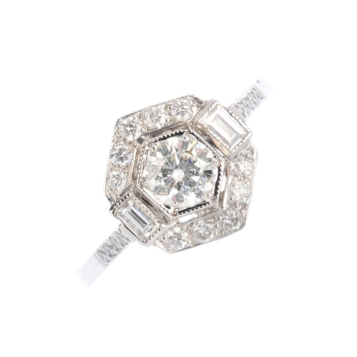 399 - A diamond cluster ring. Of hexagonal outline, the brilliant-cut diamond, with vari-cut diamond surro...