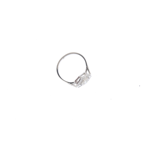 399 - A diamond cluster ring. Of hexagonal outline, the brilliant-cut diamond, with vari-cut diamond surro...