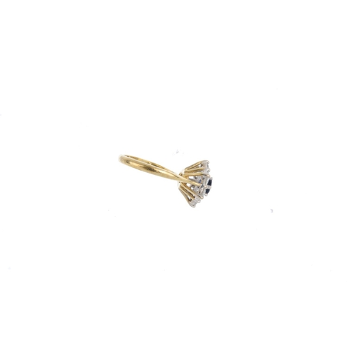 4 - An 18ct gold sapphire and diamond cluster ring. The circular-shape sapphire, with brilliant-cut diam...