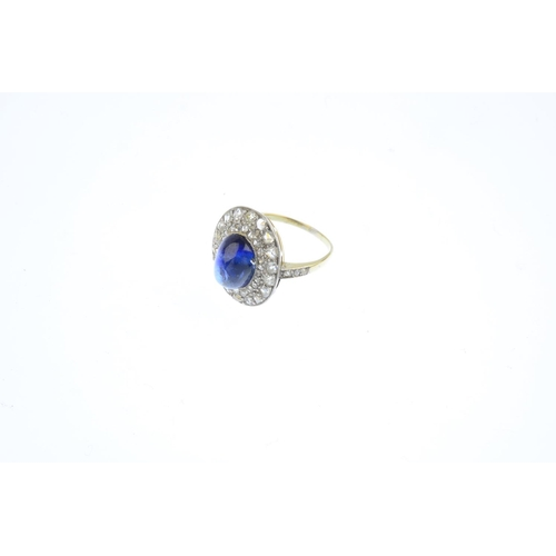 401 - A Ceylon sapphire and diamond cluster ring. The oval sapphire cabochon, weighing 5.94cts, with vari-...