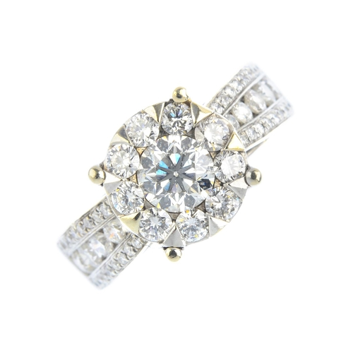 405 - A diamond cluster ring. The brilliant-cut diamond, with similarly-cut diamond surround and graduated...