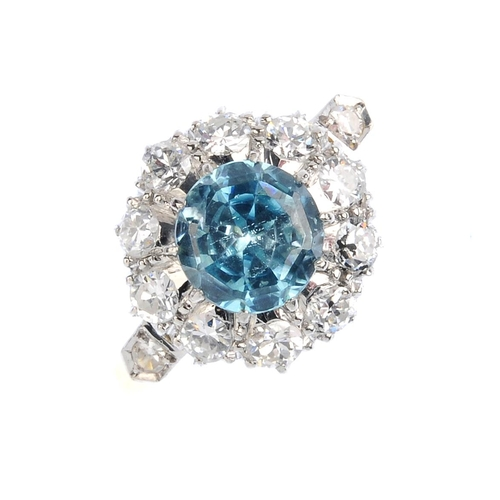 406 - A zircon and diamond cluster ring. The circular-shape blue zircon, with brilliant-cut diamond surrou...