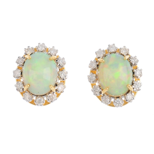 409 - A pair of 18ct gold opal and diamond cluster earrings. Each designed as an oval opal cabochon, with ...