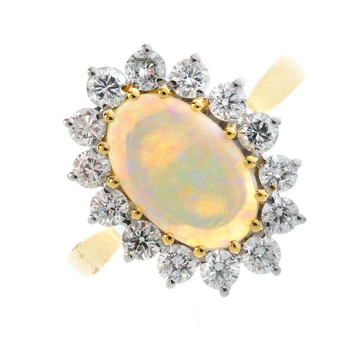413 - An 18ct gold opal and diamond cluster ring. The oval opal cabochon, with brilliant-cut diamond surro...
