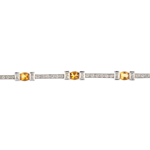 421 - A diamond and citrine bracelet. The oval-shape citrine, with brilliant-cut diamond bar sides and spa...
