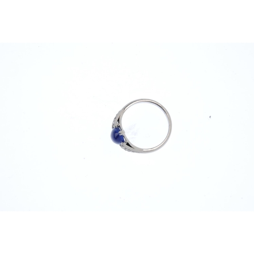 443 - A sapphire and diamond ring. The oval sapphire cabochon, with single-cut diamond line open shoulders...