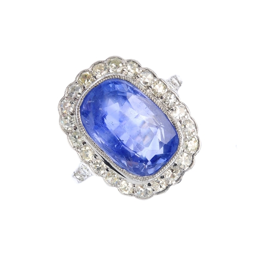 448 - A Ceylon sapphire and diamond cluster ring. The cushion-shape sapphire, weighing 7.97cts, with singl...