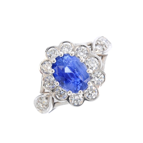 450 - A Sri Lankan sapphire and diamond cluster ring. The oval-shape sapphire, with brilliant-cut diamond ...