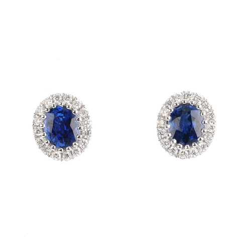452 - A pair of sapphire and diamond earrings. The oval-shape sapphire, with brilliant-cut diamond surroun...
