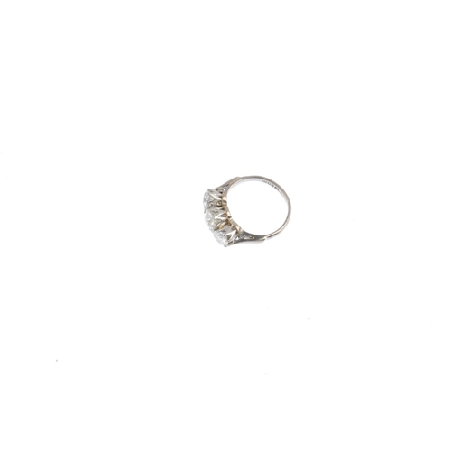 456 - A diamond three-stone ring. Designed as a graduated vari-cut diamond line, with tapered shoulders. E...