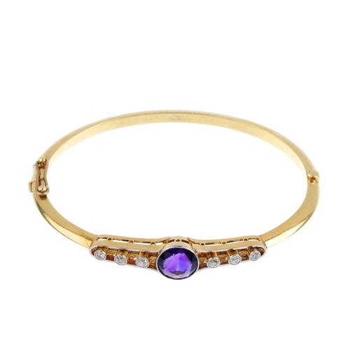 459 - An early 20th century amethyst and diamond hinged bangle. Of openwork design, the circular-shape ame...