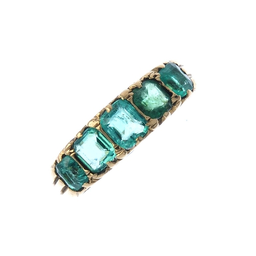 461 - An emerald five-stone ring. The cushion-shape emerald line, with scrolling gallery and grooved shoul...