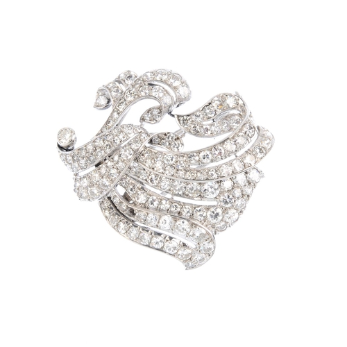 465 - A diamond brooch. Designed as a vari-cut diamond scrolling foliate spray. Estimated total diamond we...