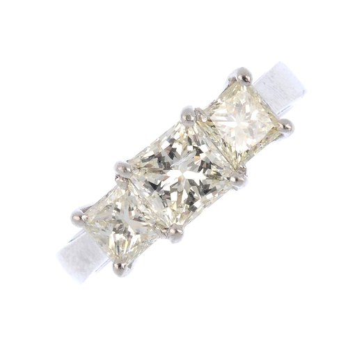 469 - A diamond three-stone ring. The square-shape diamond graduated line, to the tapered band. Estimated ...